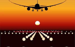 Flugzeug landet auf einer Landebahn, während die Sonne untergeht.