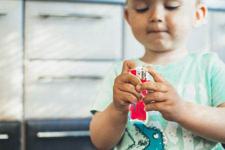 Kleinkind mit einem rosa roten Feuerzeug